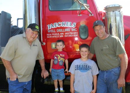 4 Generations of Jaeckels Well Drilling Inc boys in front of red truck